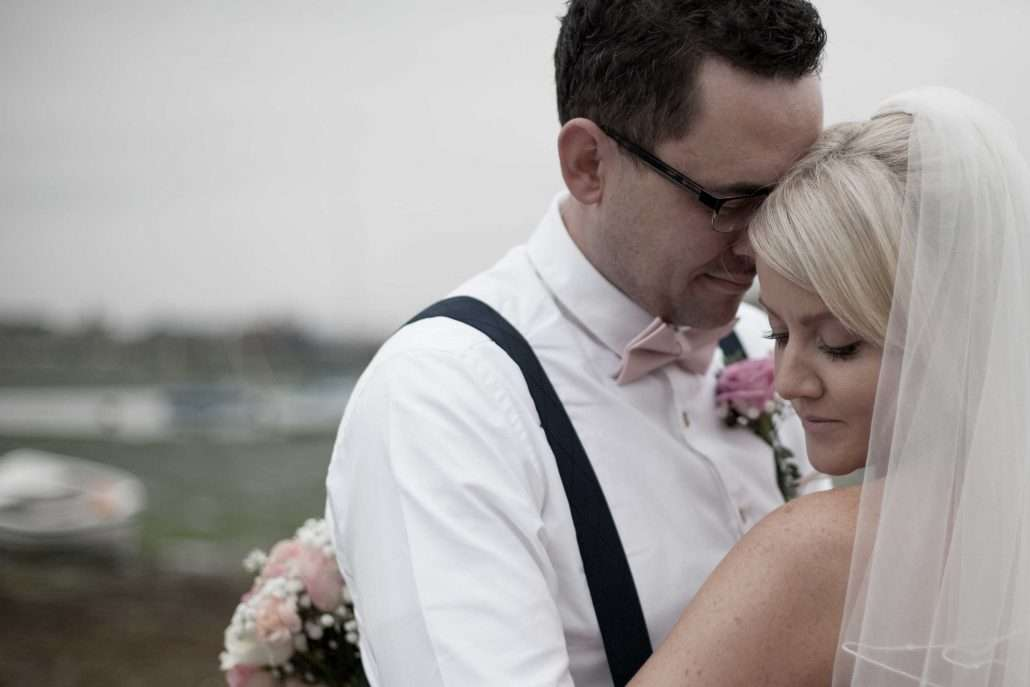 A wedding photo of a bride and groom at Bosham harbour in Chichester