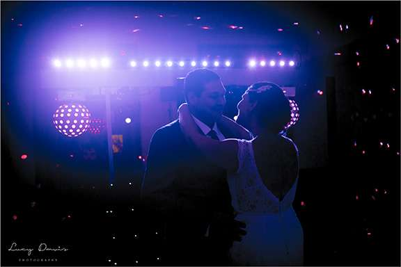 A photo of a Bride and groom dancing at their wedding backlit by the stage lighting