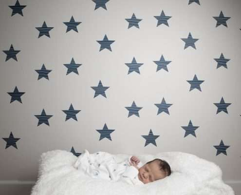 A photo of a baby in front of star wallpaper