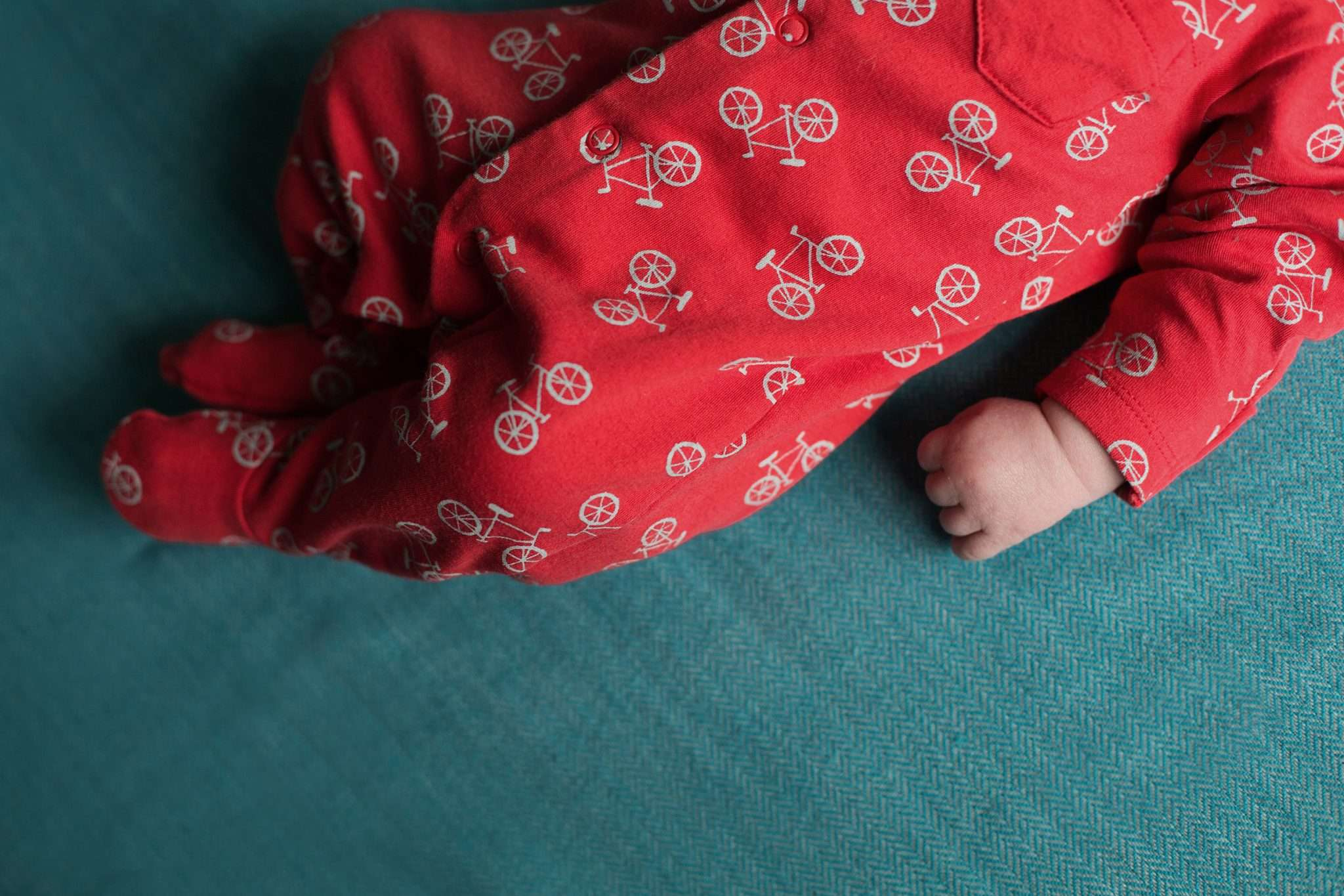 A photo of a babys hand with bright coloured babygrow and blanket
