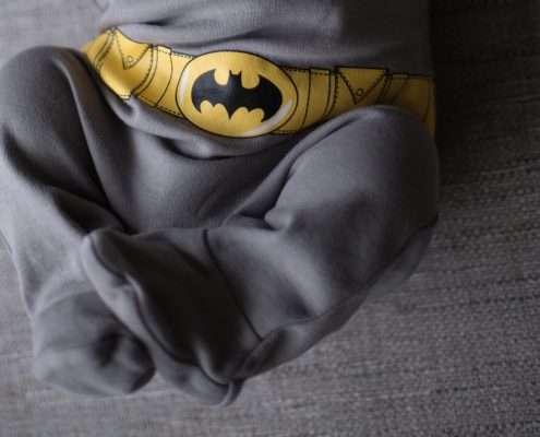 A photo of a newborn baby wearing a batman costume