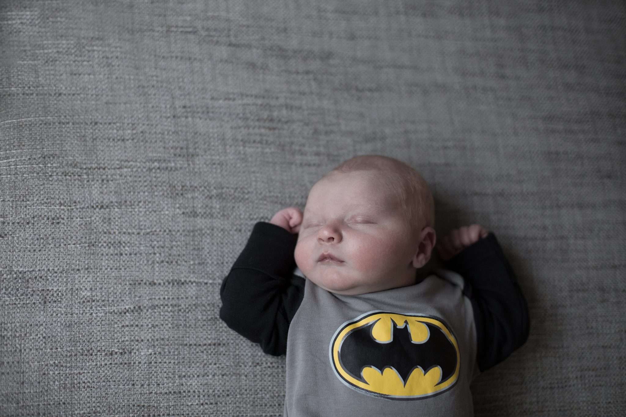 A photo of a newborn baby wearing a batman costume