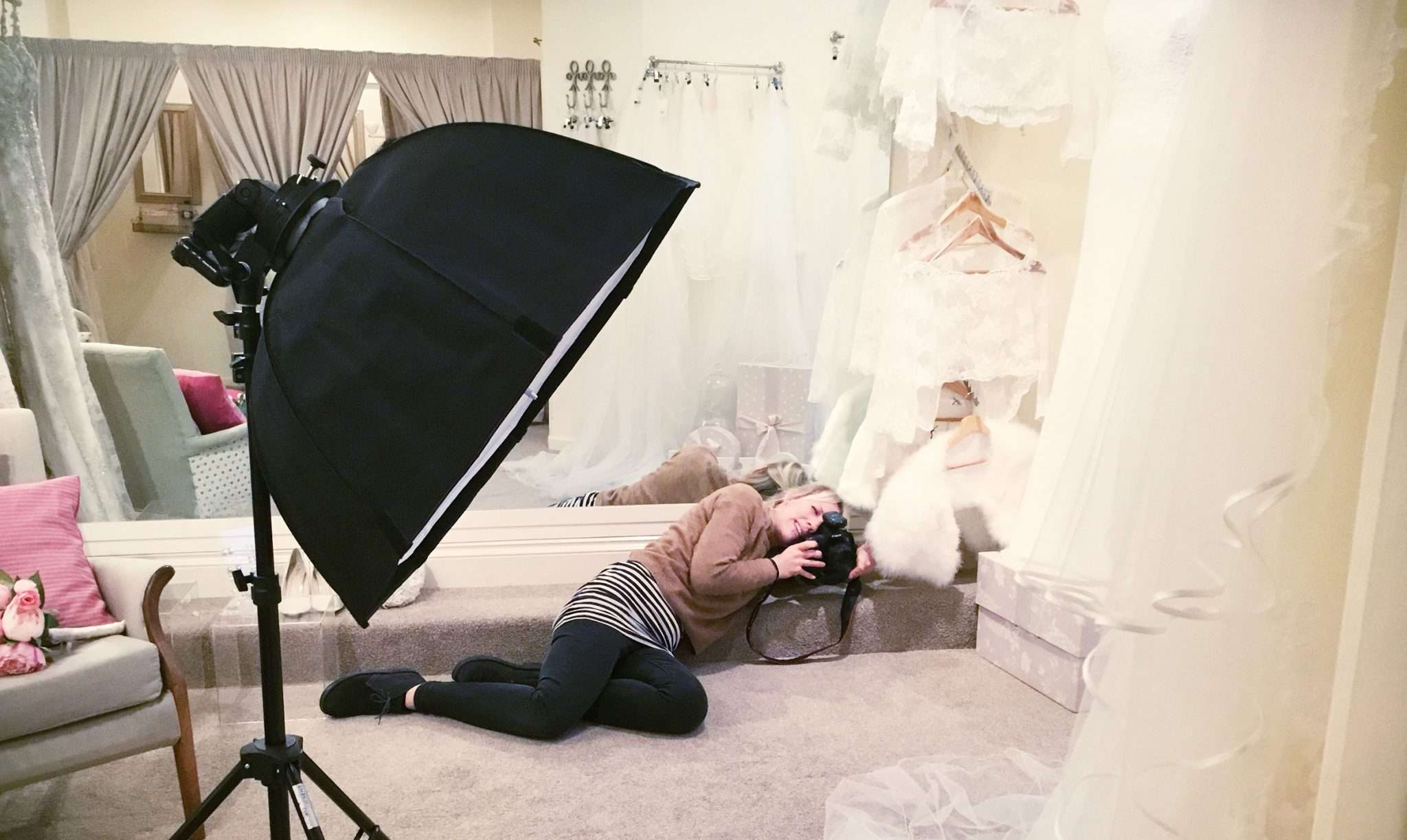A photo of a female photographer taking a photo in a bridal boutique