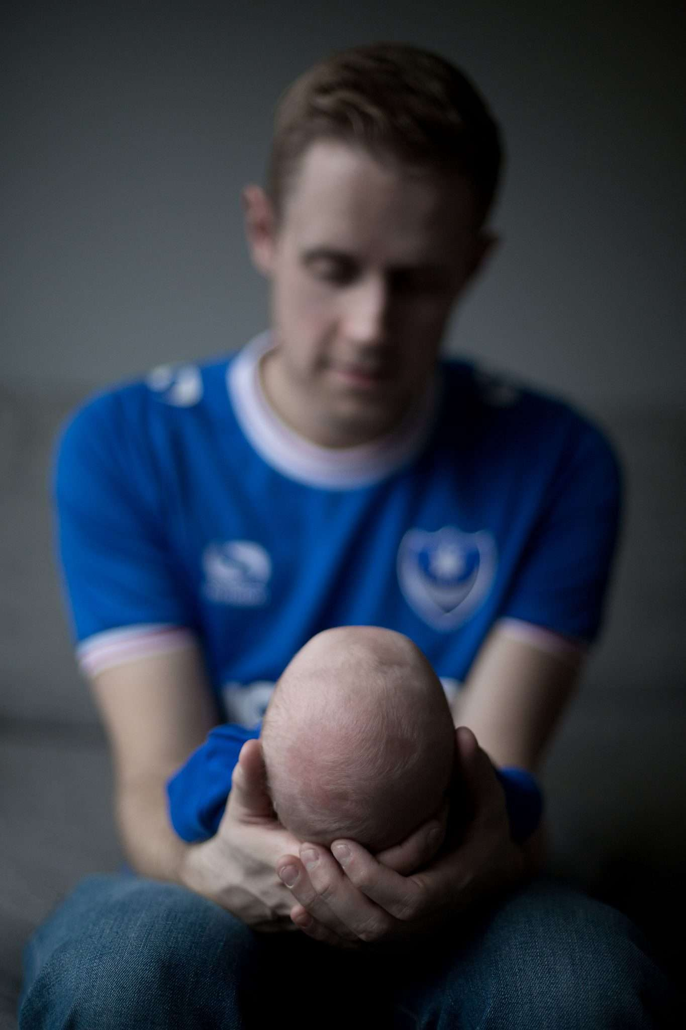 A photo of a man holding a baby wearing a blue t-shirt