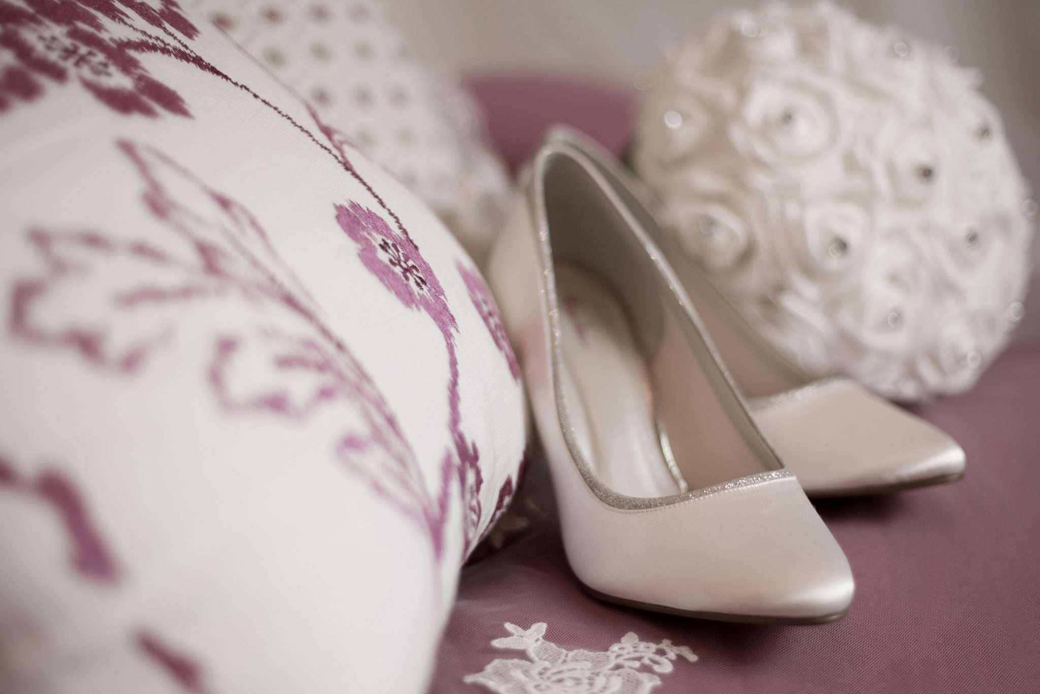 A photo of a pair of white bridal shoes and bouquet on a pink sofa