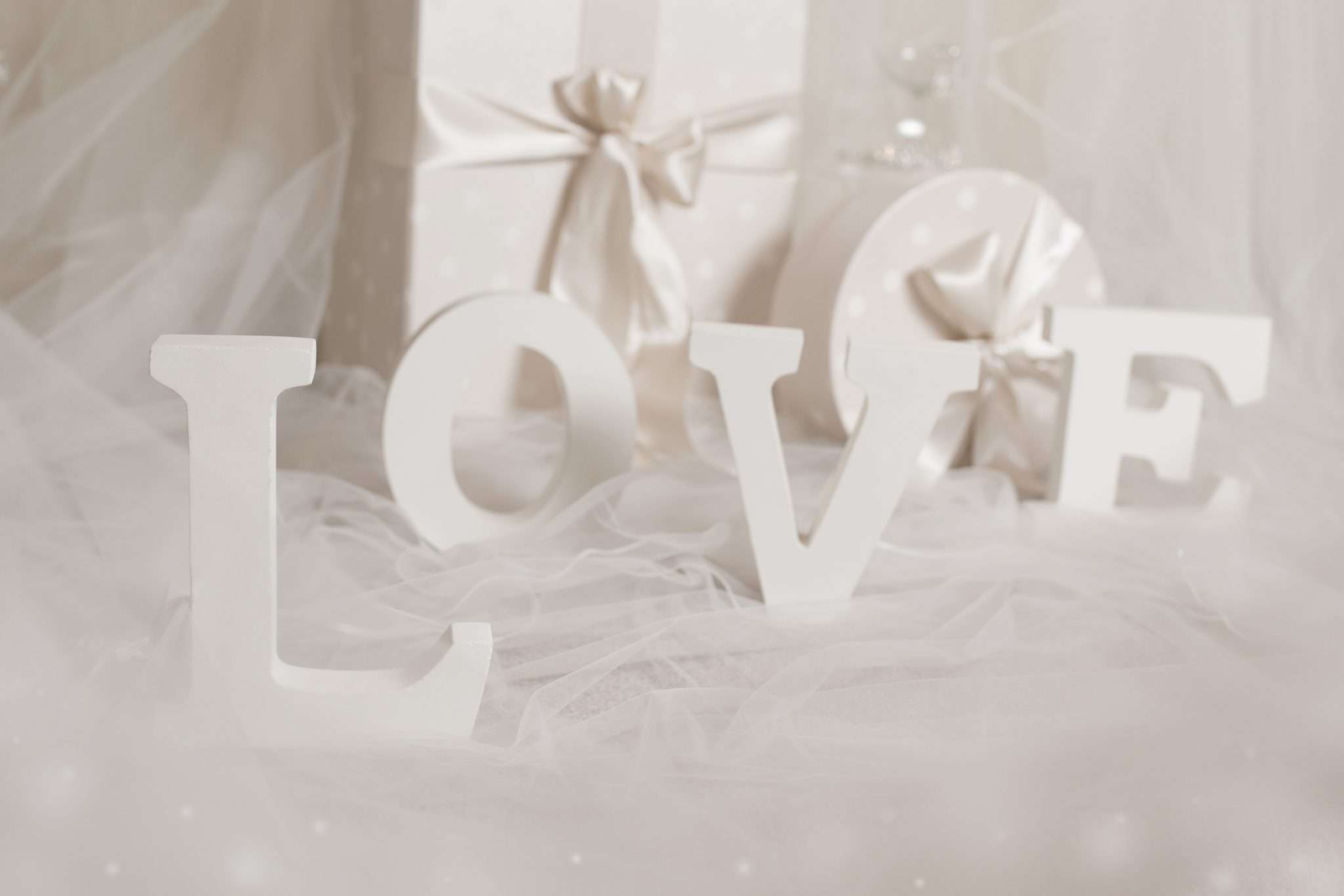 A photo of white wooden letters L O V E on a bridal veil with a ribbon wrapped box. box