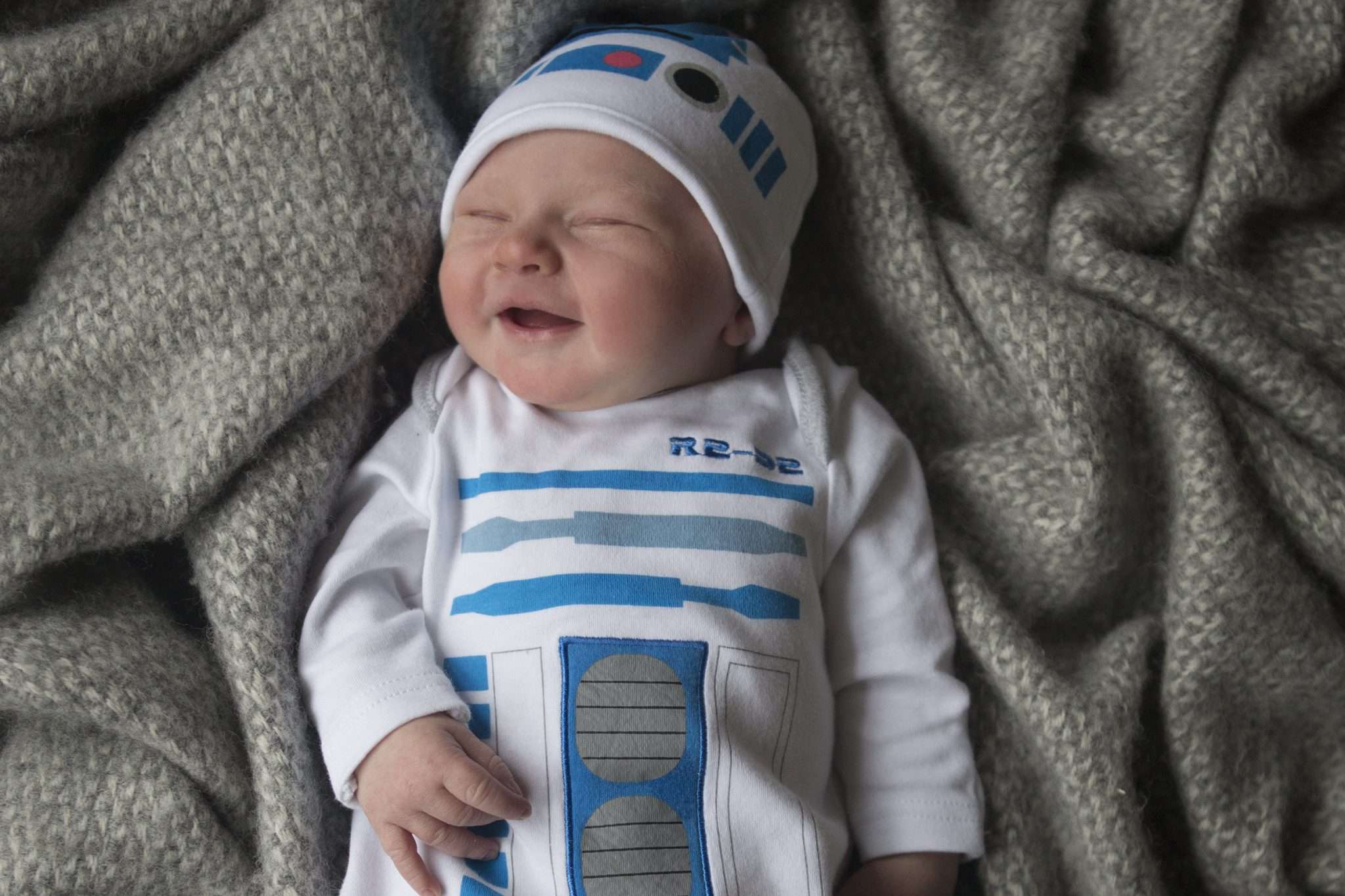 A photo of a smiling newborn baby wearing an R2D2 Starwars outfit