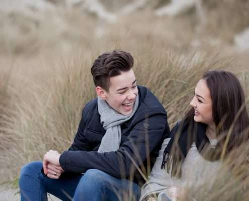 A photo of a teenage girl and boy wearing coats sitting in grasses, laughing at the beach.