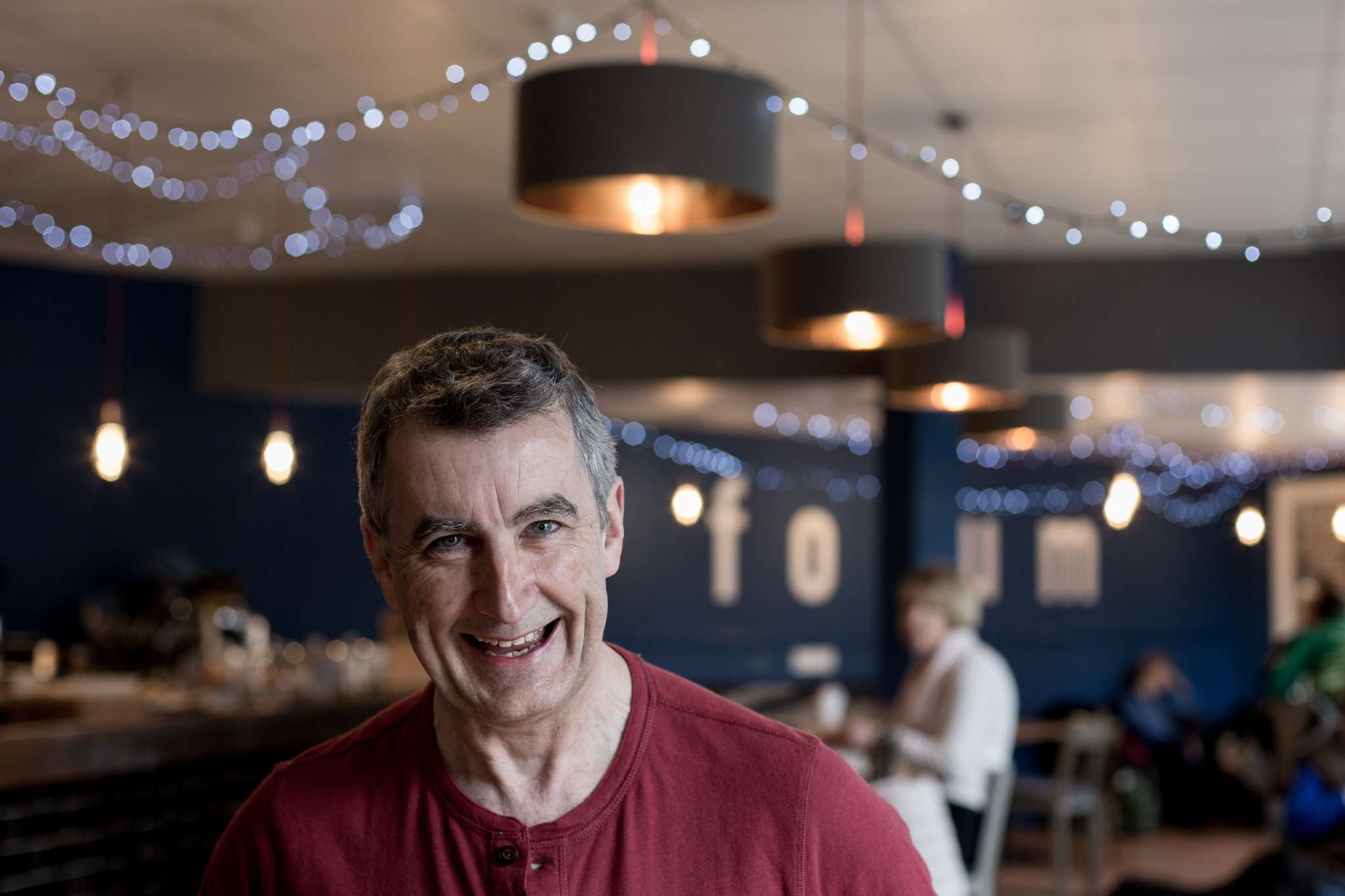 A headshot portrait photo of a man in a cafe in Chichester