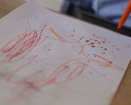 A photo of a toddler felt tip pen drawing with red and orange