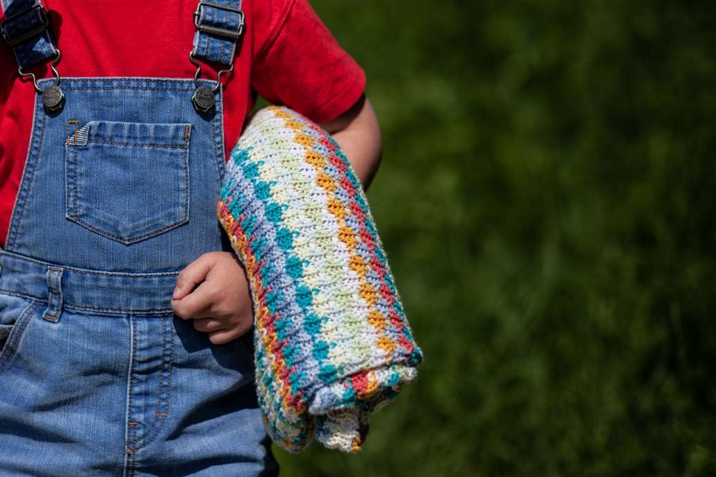 A photo of a boy in dungarees holding a bright coloured blankett