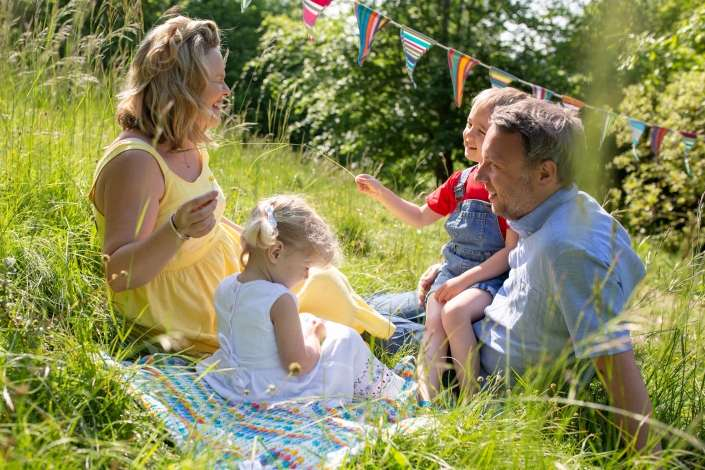 A lifestyle portrait photo of a family on a blanket in a grassy field in Arundel