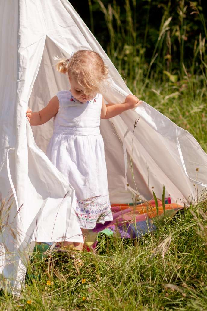 A lifestyle portrait photo of a little girl in a white teepee in a field in Arundel