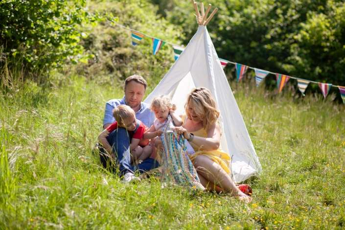 A lifestyle portrait photo of a family on a blanket in a grassy field with a teepee in Arundel