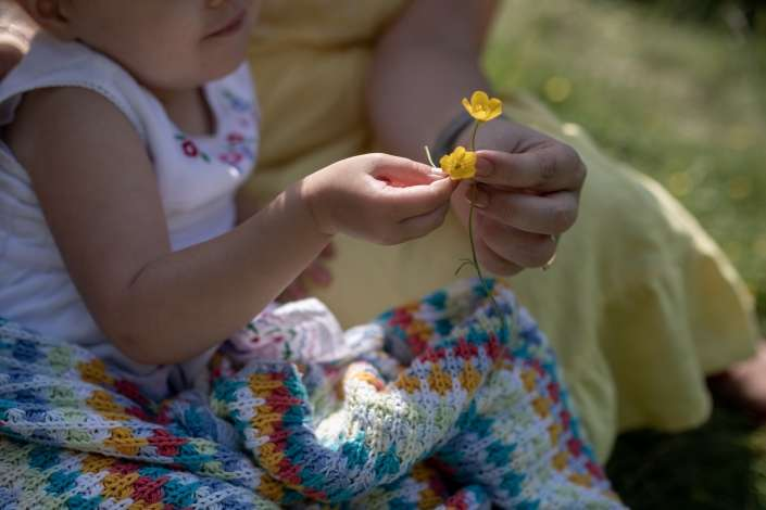 A location portrait photo of a little girl and mother holding a buttercup in Arundel