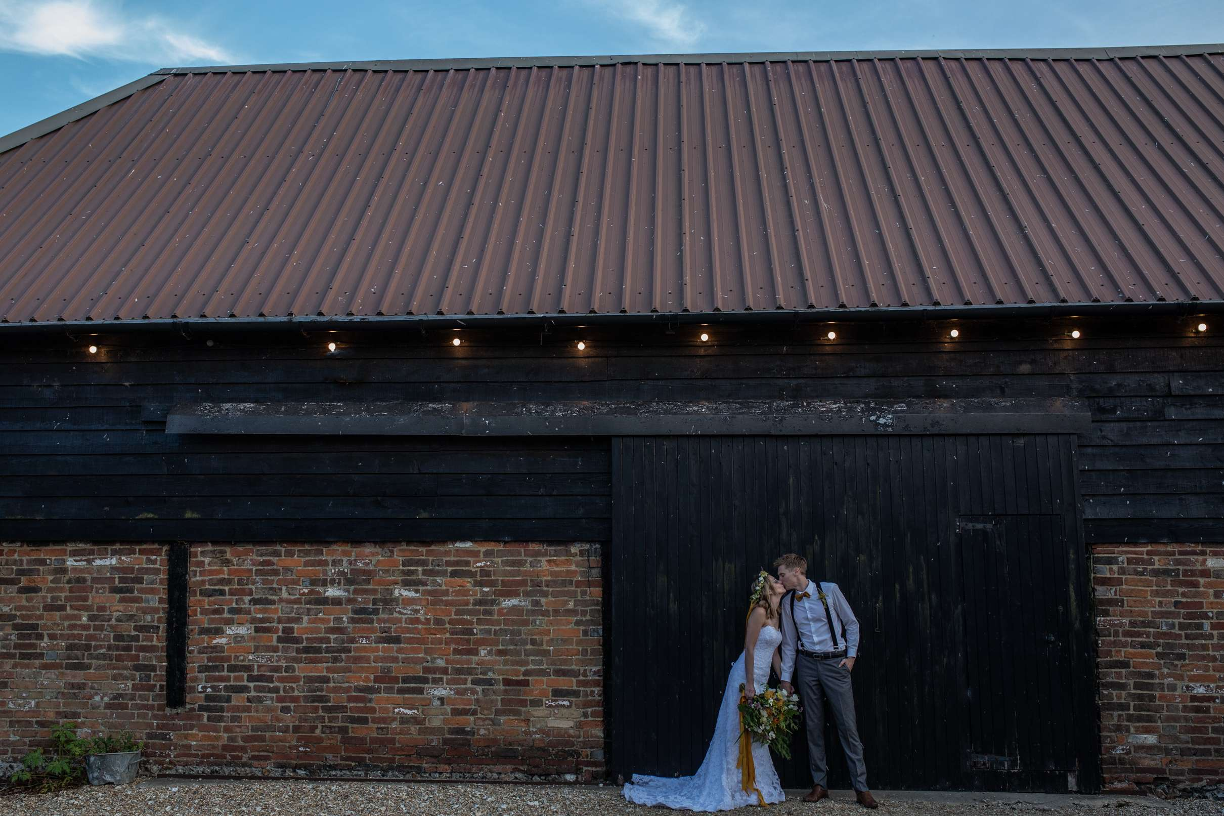 A wedding photo in Chichester a bgroom standing by a wooden clad wall, taken at Chidham barn