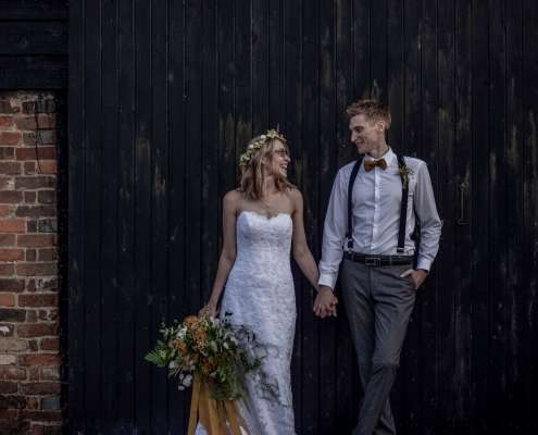A wedding photo in Chichester a bride and groom standing by a wooden clad wall, taken at Chidham barn