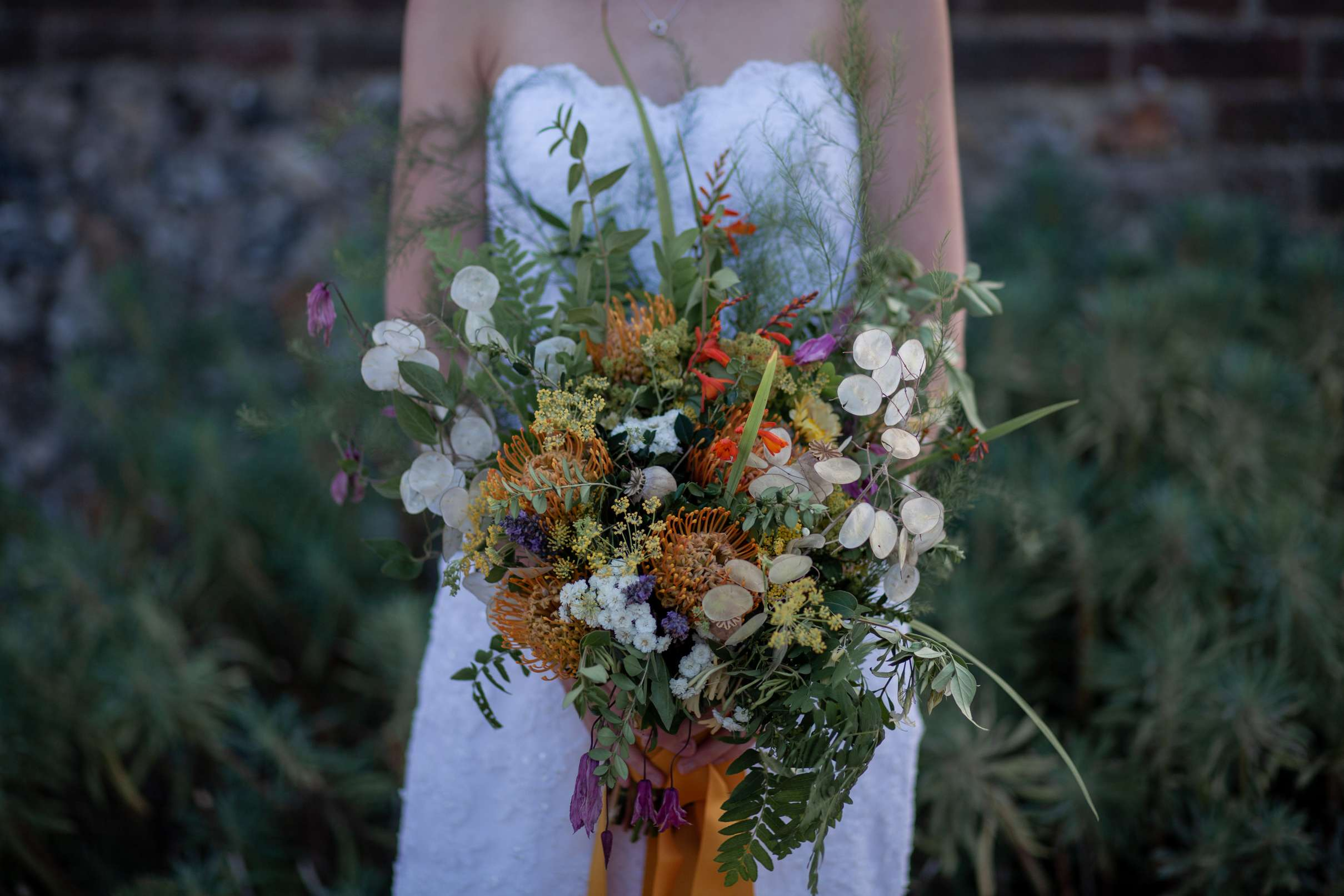 A wedding photo in Chichester a close up of a bride holding a rustic bouquet, taken at Chiddham barn