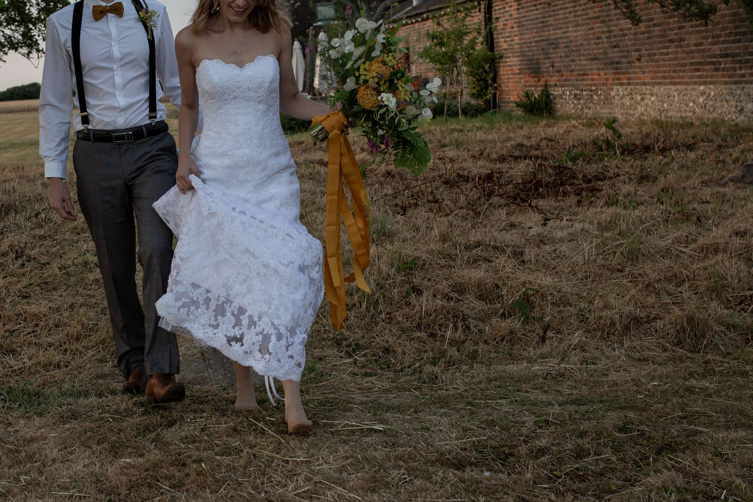 A wedding photo of a bride and groom walking along, taken at Chidham barn, Chichester