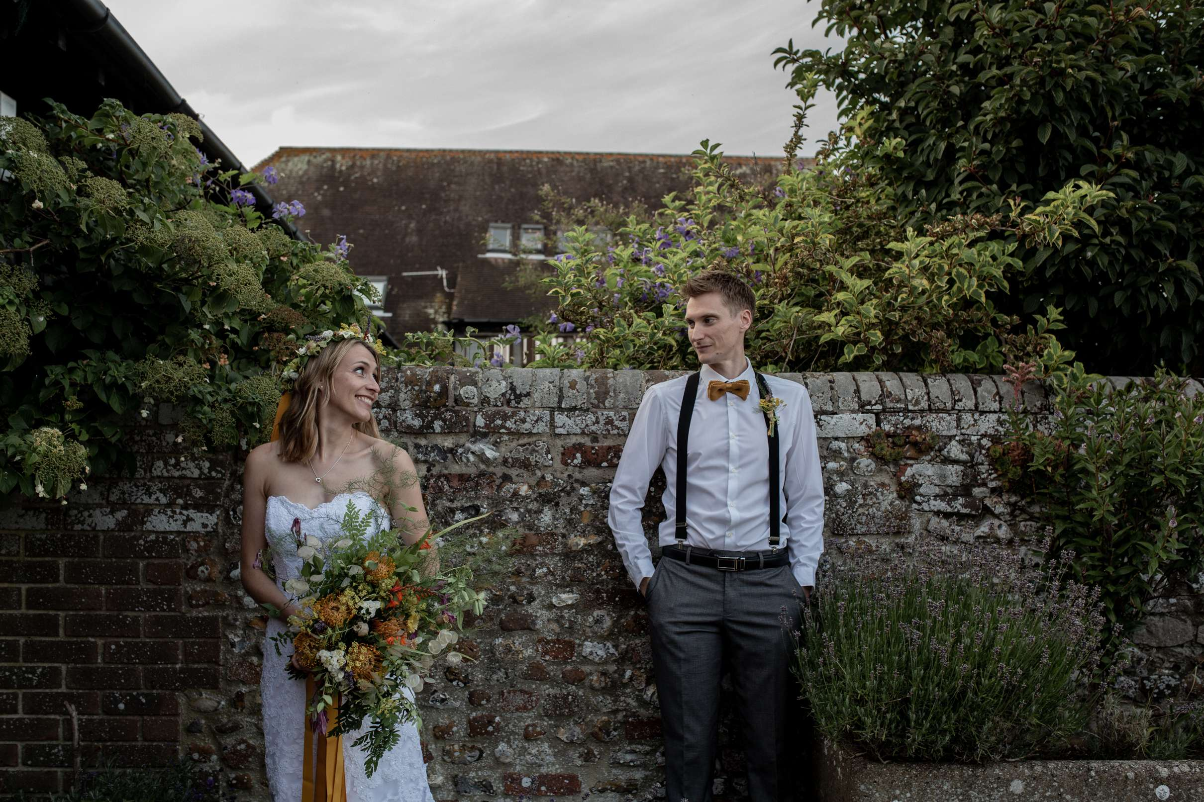 A wedding photo in Chichester of a bride and groom standing by a beautiful rustic wall, taken at Chidham barn