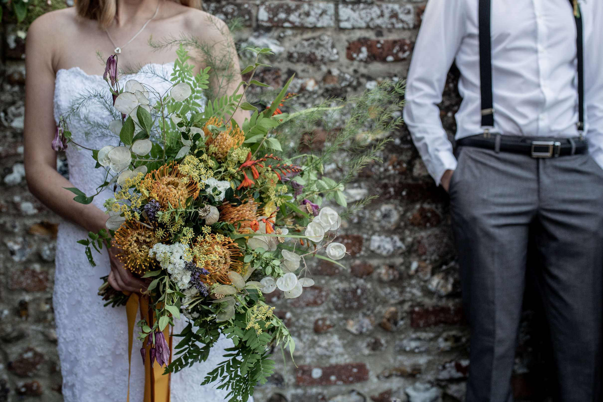 A wedding photo in Chichester a close up of a bride holding a rustic bouquet with the groom in the background, taken at Chiddham barn