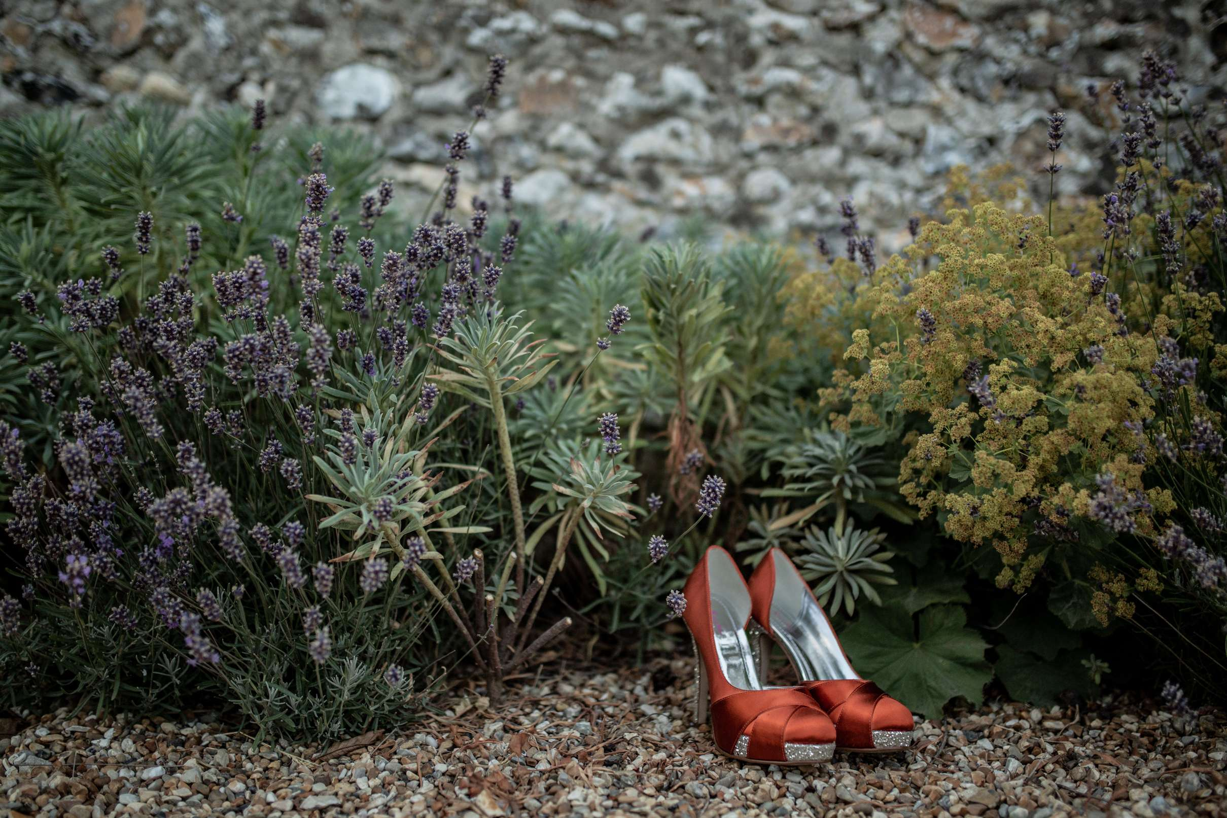 A photo of orange wedding shoes taken against a rustic backdrop at Chidham barn, Chichester