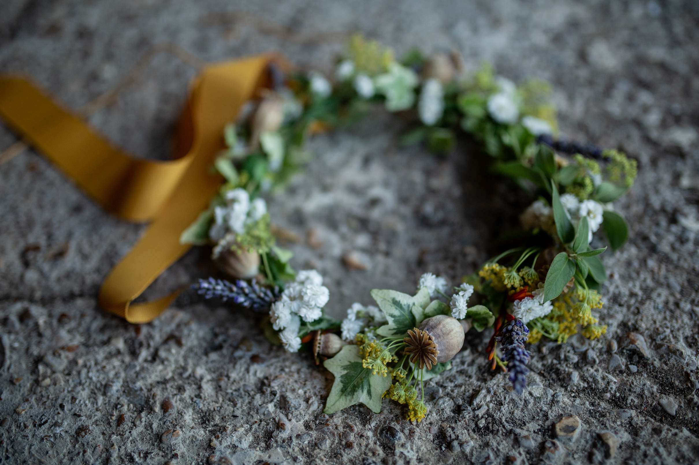 A wedding photo in Chichester of a rustic floral headdres with ivy and poppy pods placed against a concrete backdrop, taken at Chidham barn
