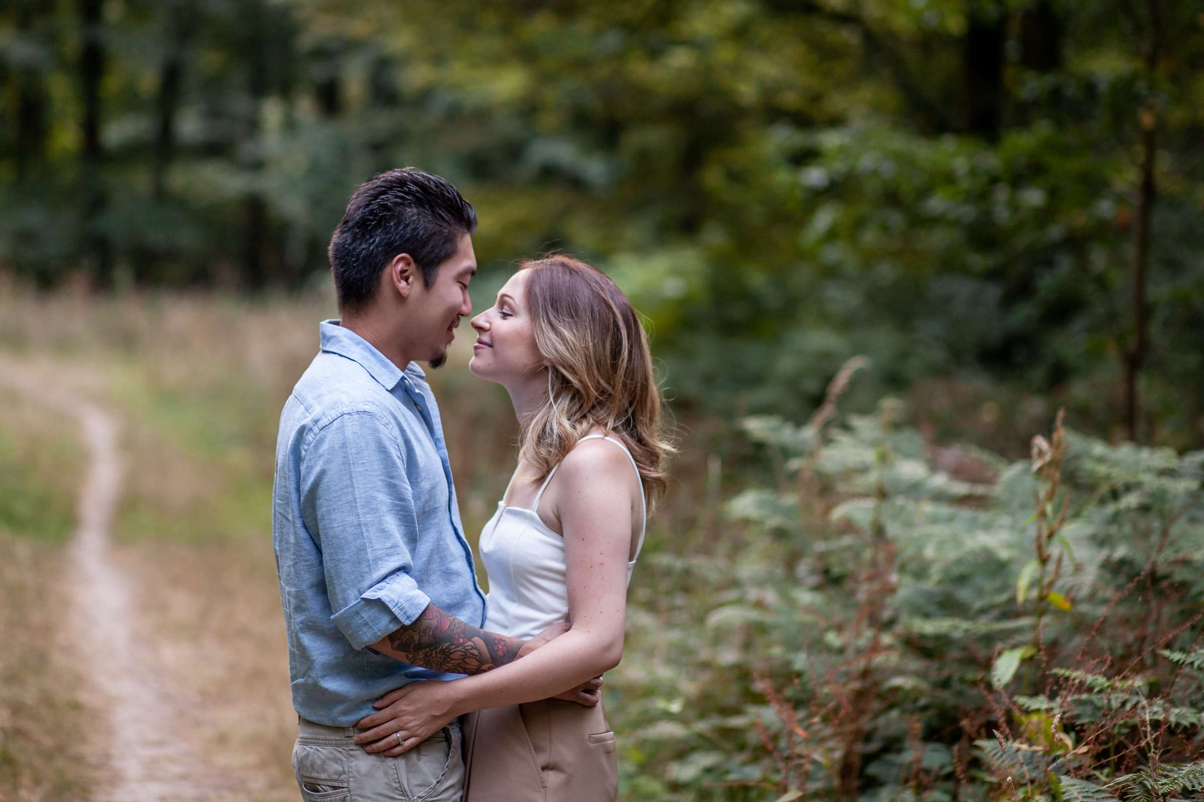 A portrait photo of a couple looking at each other and laughing in the woods having an engagement session in Chichester, West Sussex