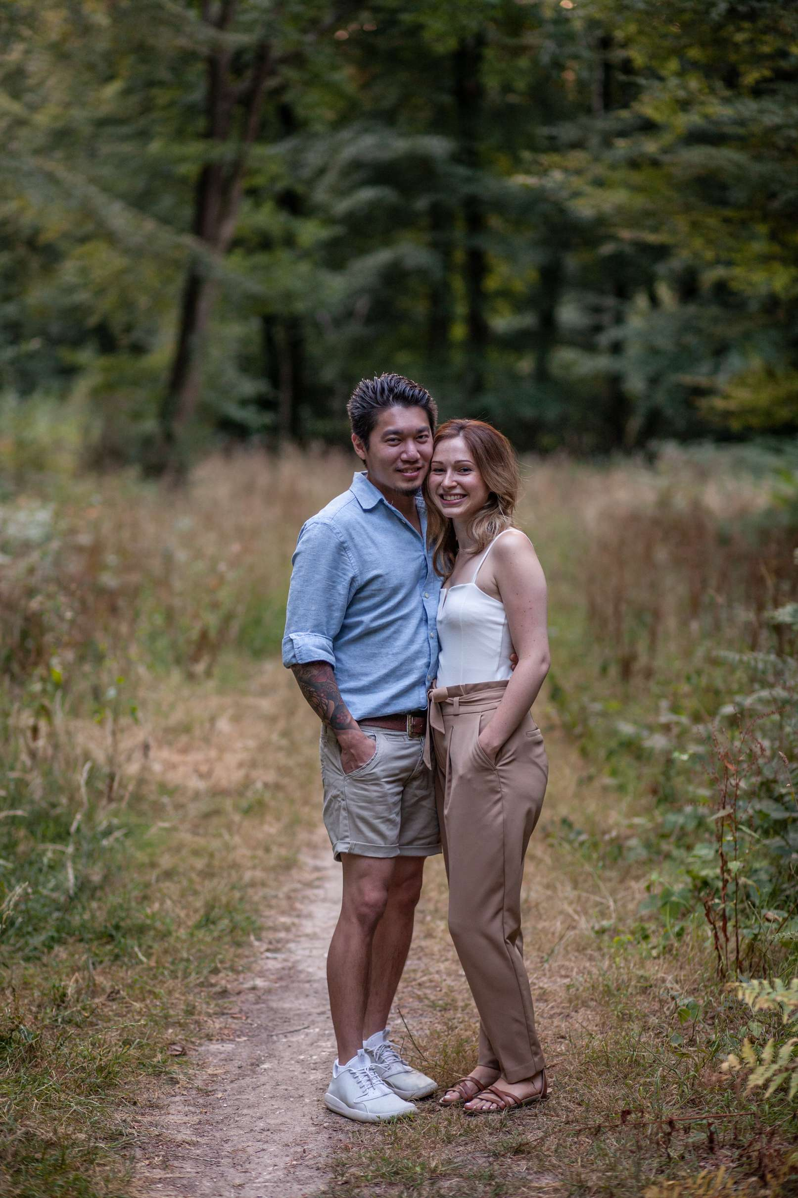 A full length portrait photo of a couple in the woods having an engagement session in Chichester, West Sussex