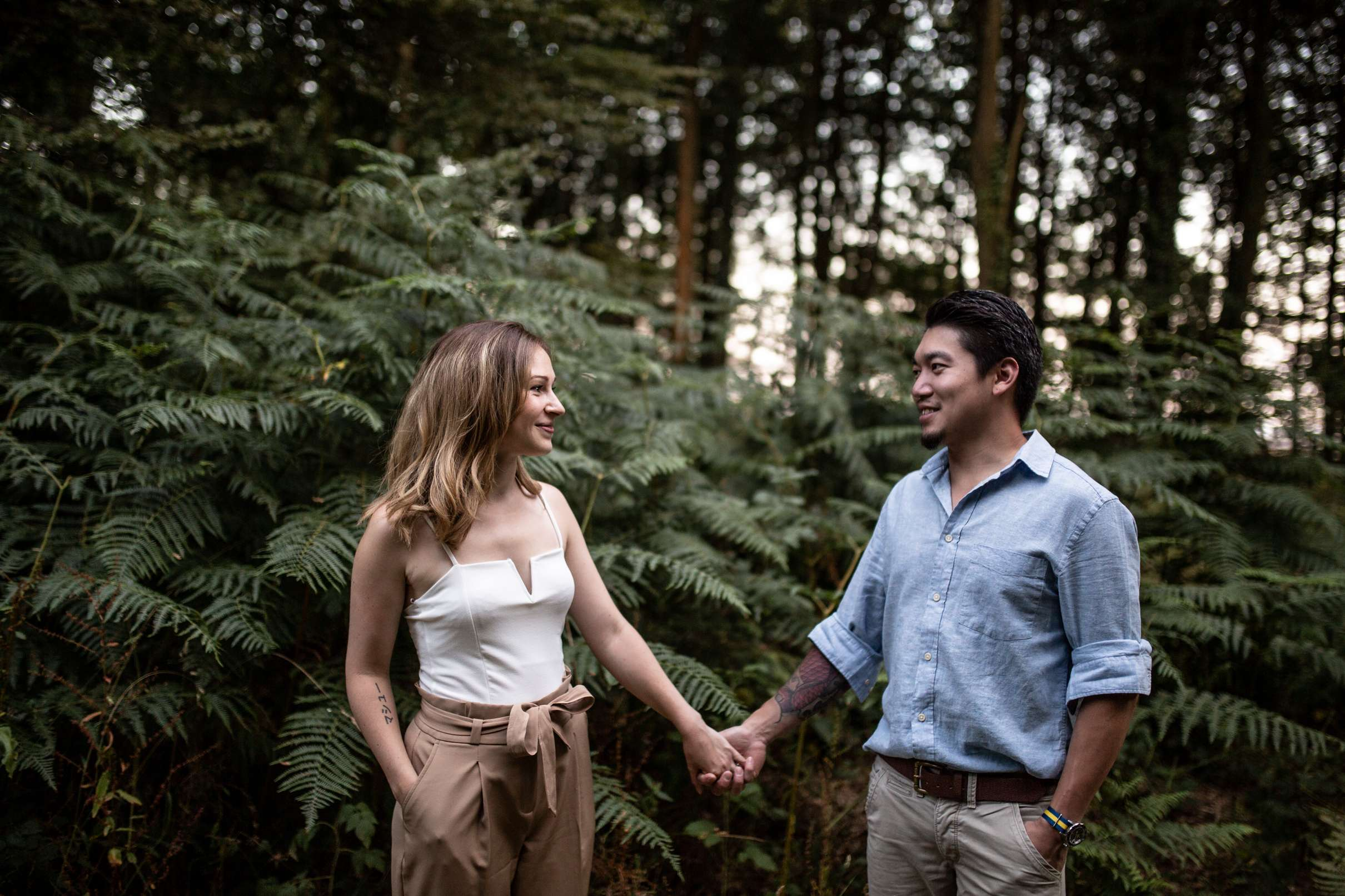 A portrait photo of a couple holding hands in the woods having an engagement session in Chichester, West Sussex