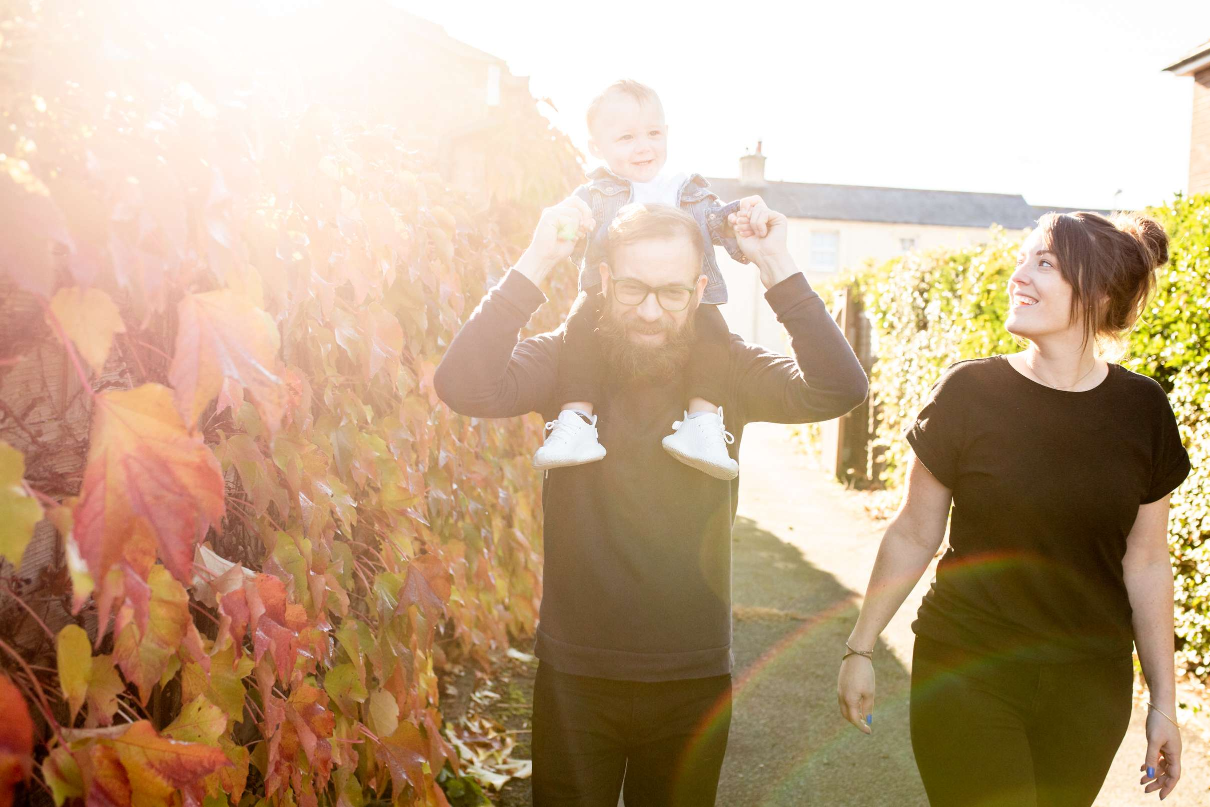 A family portrait photo of a dad with a baby on his shoulders walking with mum bu some autumn leaves