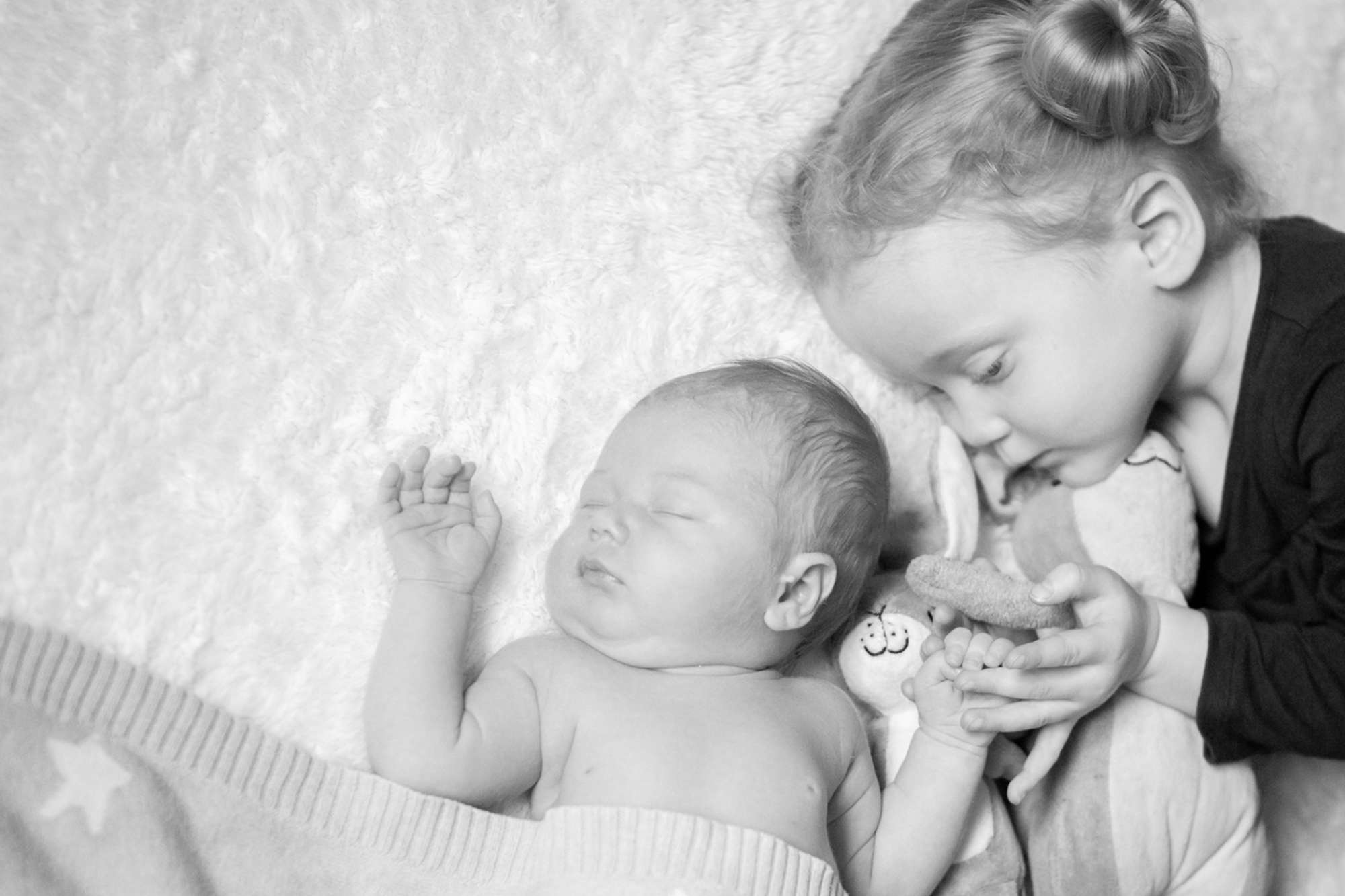 A black and white portrait photo of a newborn baby and toddler