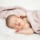 A lifestyle portrait photo of a newborn baby girl lying on a white fluffy blanket