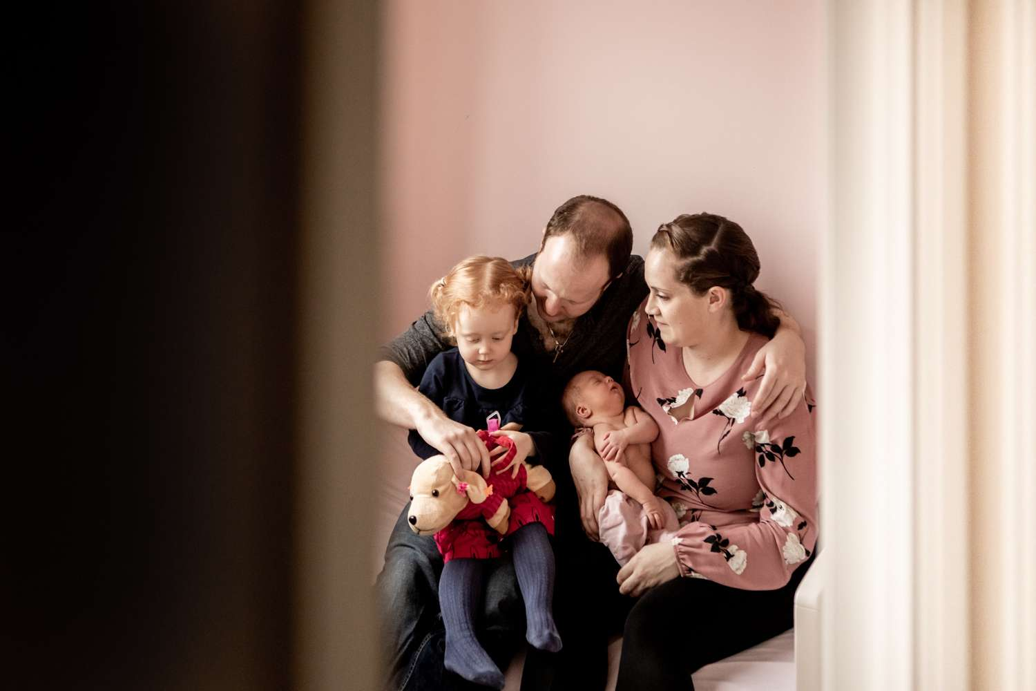 a family portrait photo of a family with toddler and newborn sat on parents laps on a bed in a pink bedroom