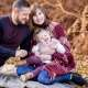 A portrait photo of a family with a toddler, sitting in front of autumn bracken