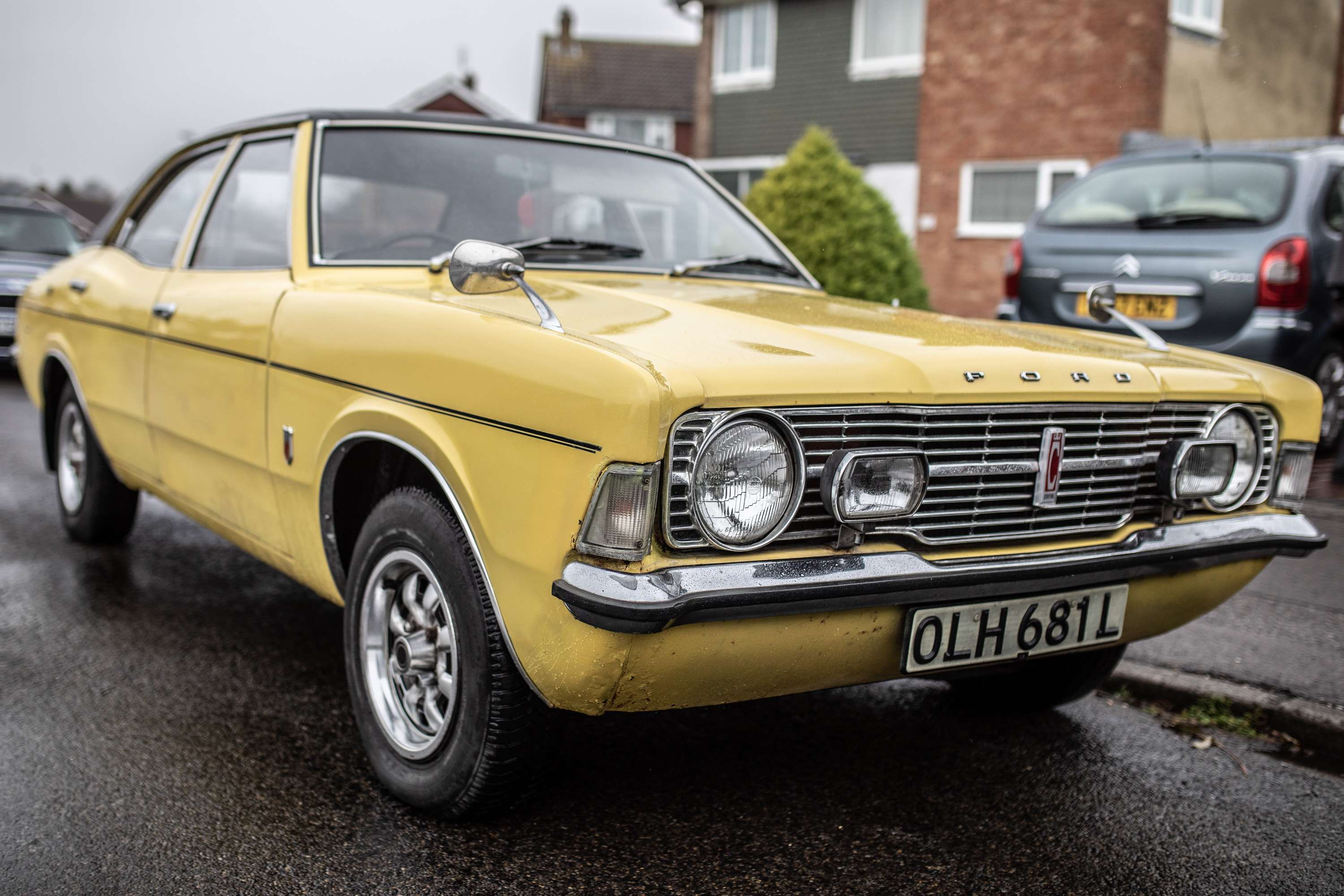 A wedding photo of a yellow ford cortina wedding car. Taken in Chichester, Sussex