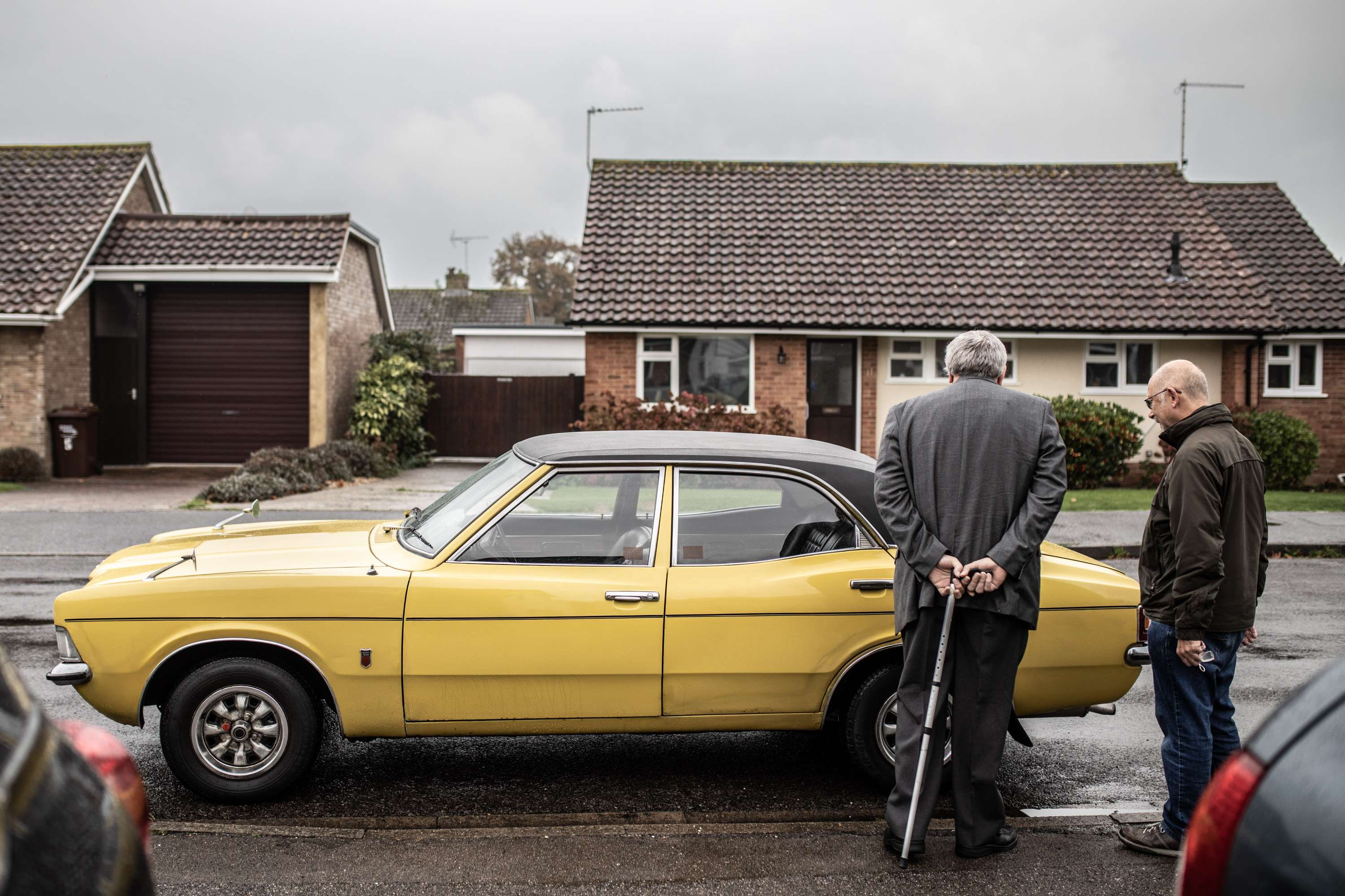 A wedding photo of father of the bride and guest looking at a yellow ford cortina wedding car. Taken in Chichester, Sussex