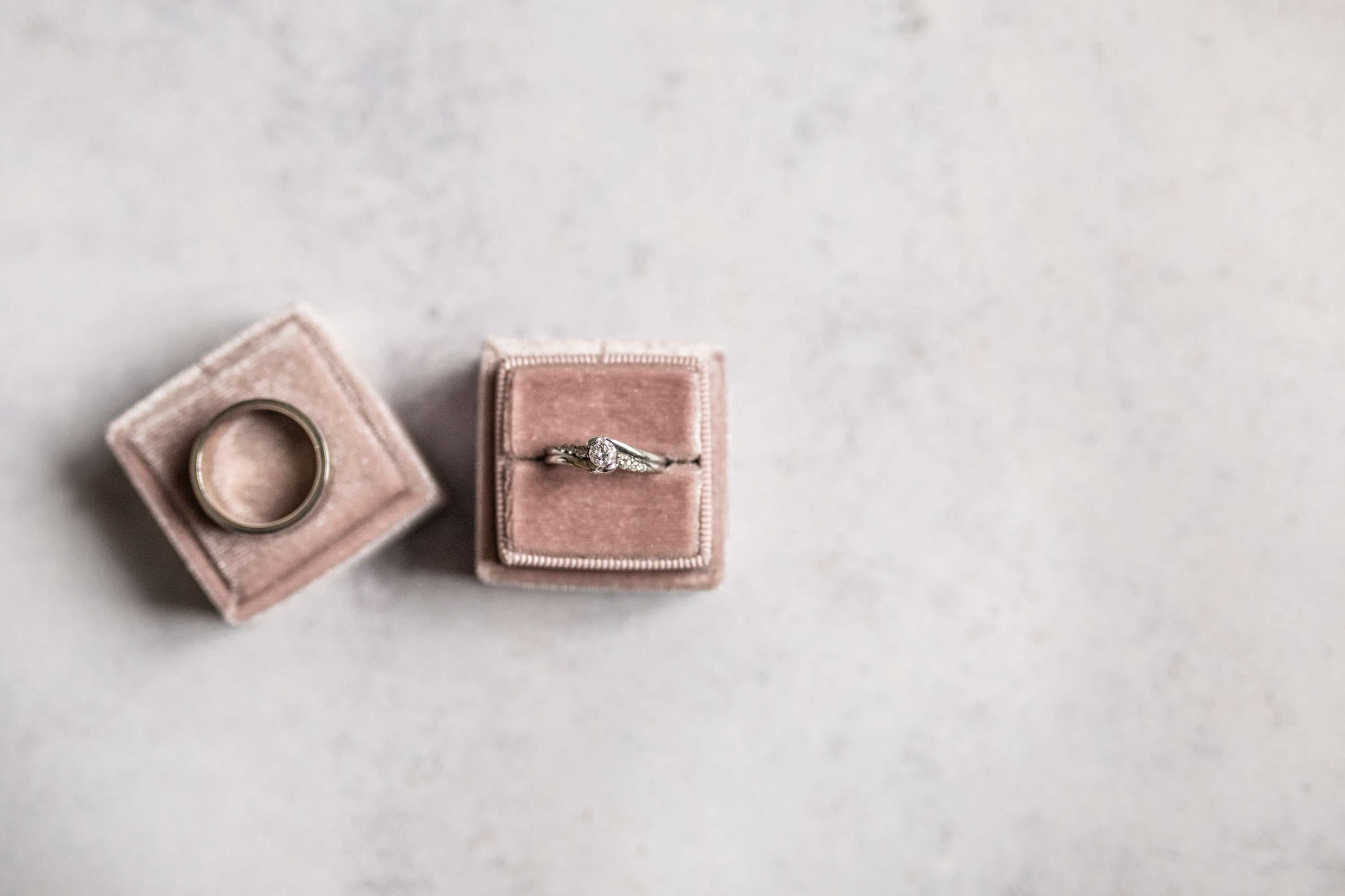 A wedding photo of bride and groom's wedding rings on a pink velvet ring box. Taken in Chichester, Sussex