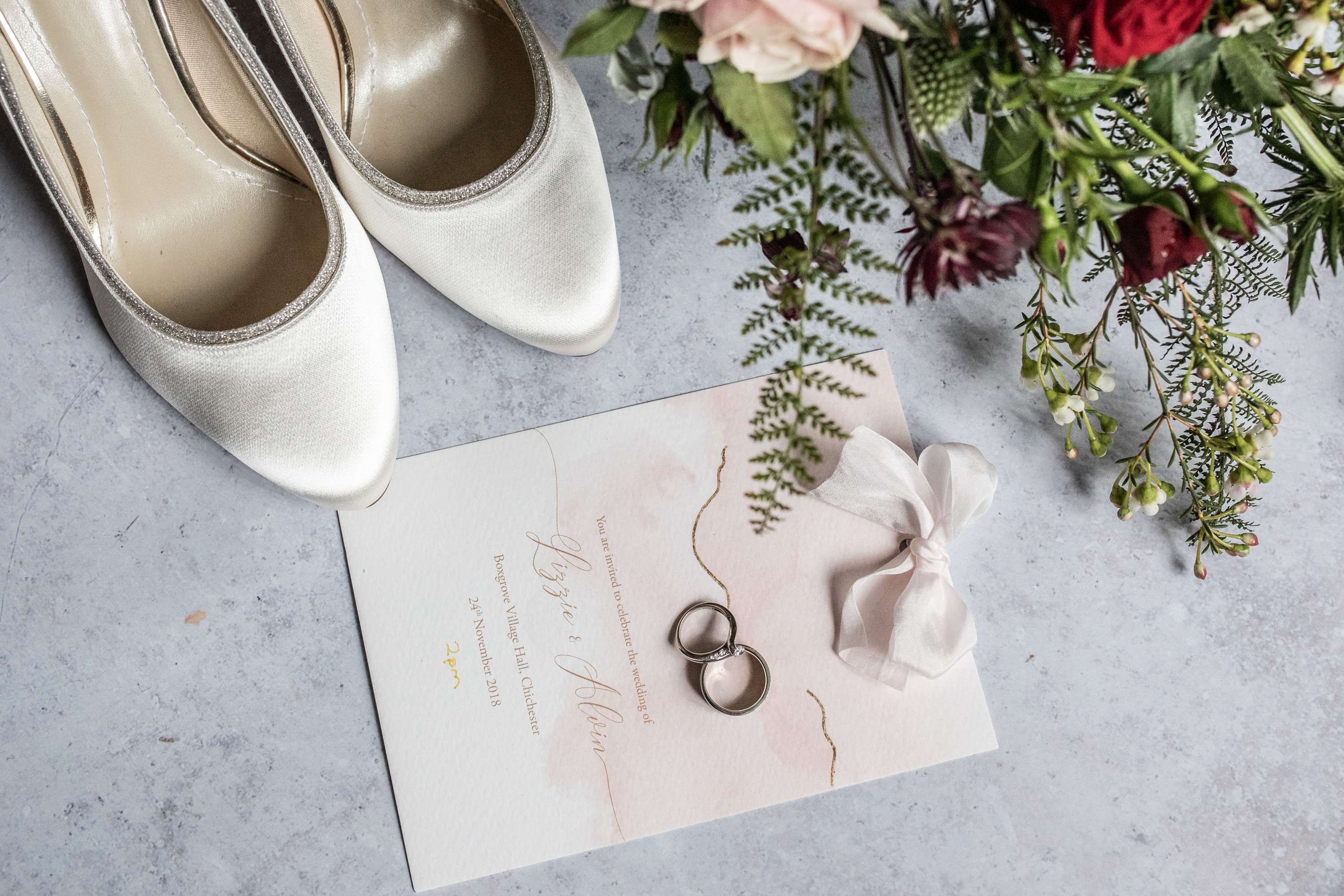 A flat lay wedding photo of bridal shoes, wedding rings and wedding bouquet. Taken in Chichester, Sussex.