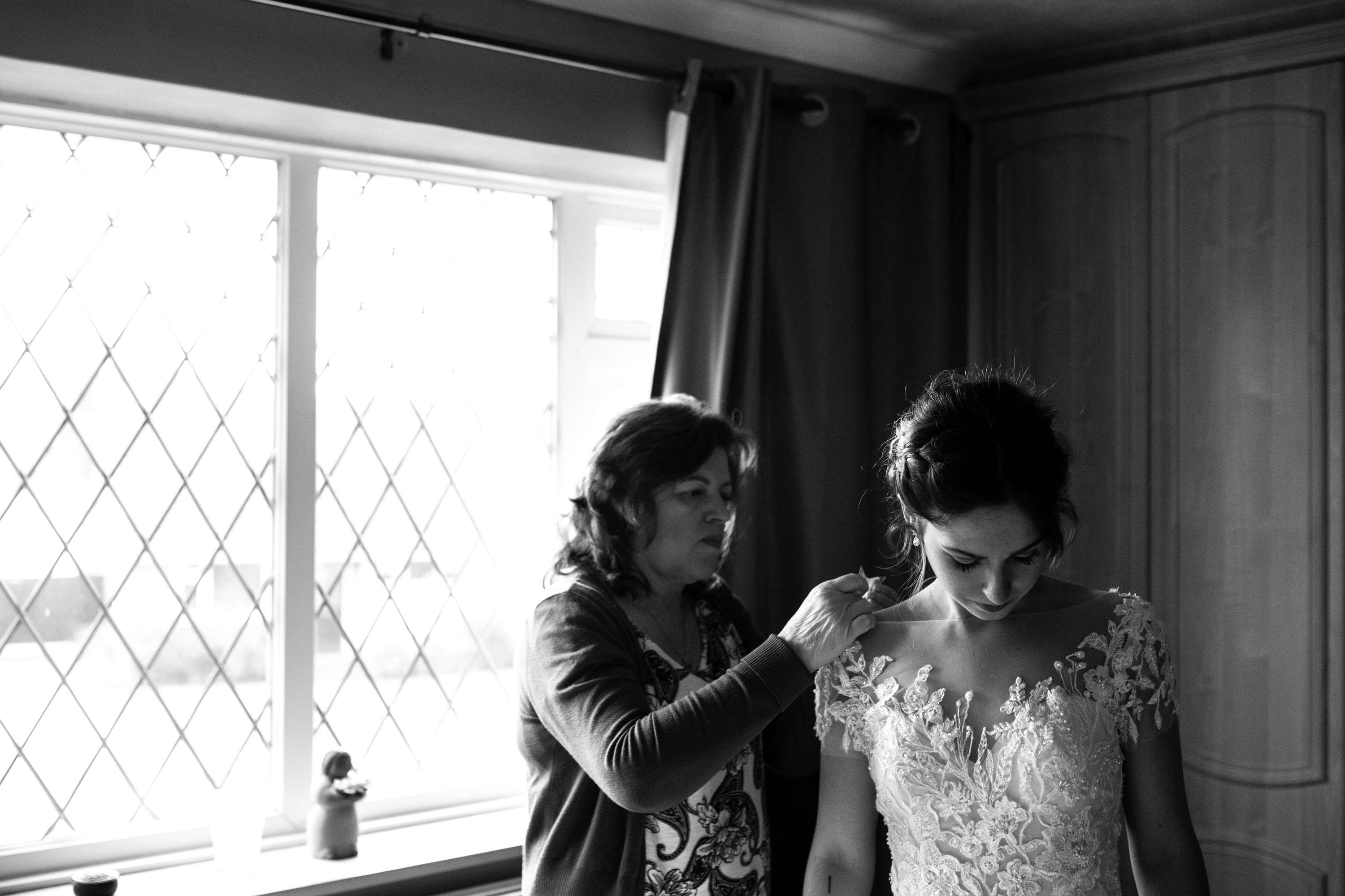 A black and white wedding photo of a bride and mother of the bride getting ready on her wedding day. Taken in Chichester, Sussex