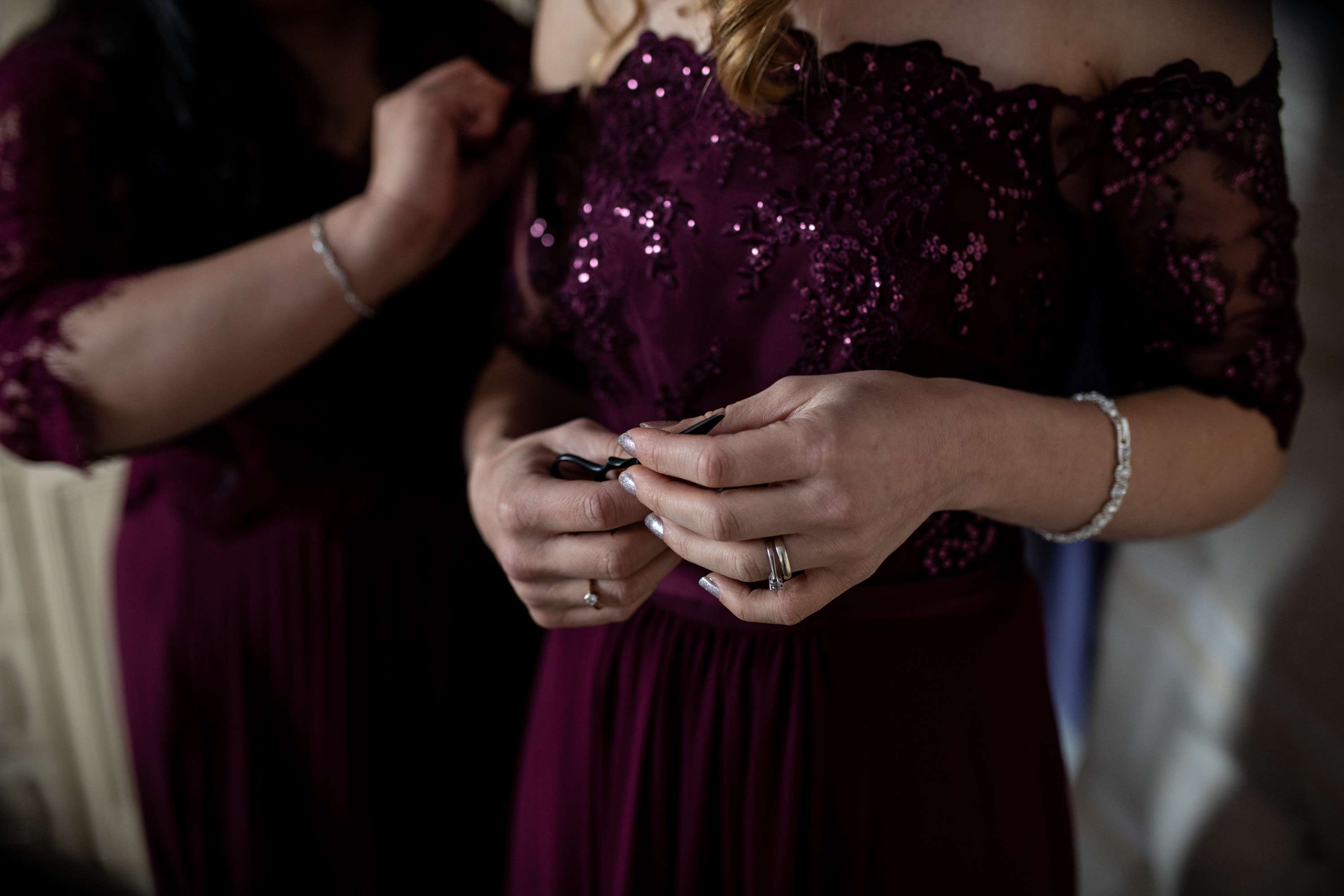 A wedding photo of a bridesmaids hands with sparkly burgundy dress behind. Taken in Chichester, Sussex