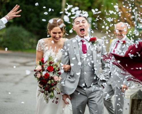 A wedding photo of a bride and groom walking through confetti. Taken at Boxgrove, near Chichester