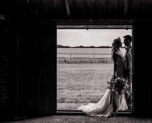 A wedding silhouette photo of a bride and groom taken in a barn doorway in Chidham