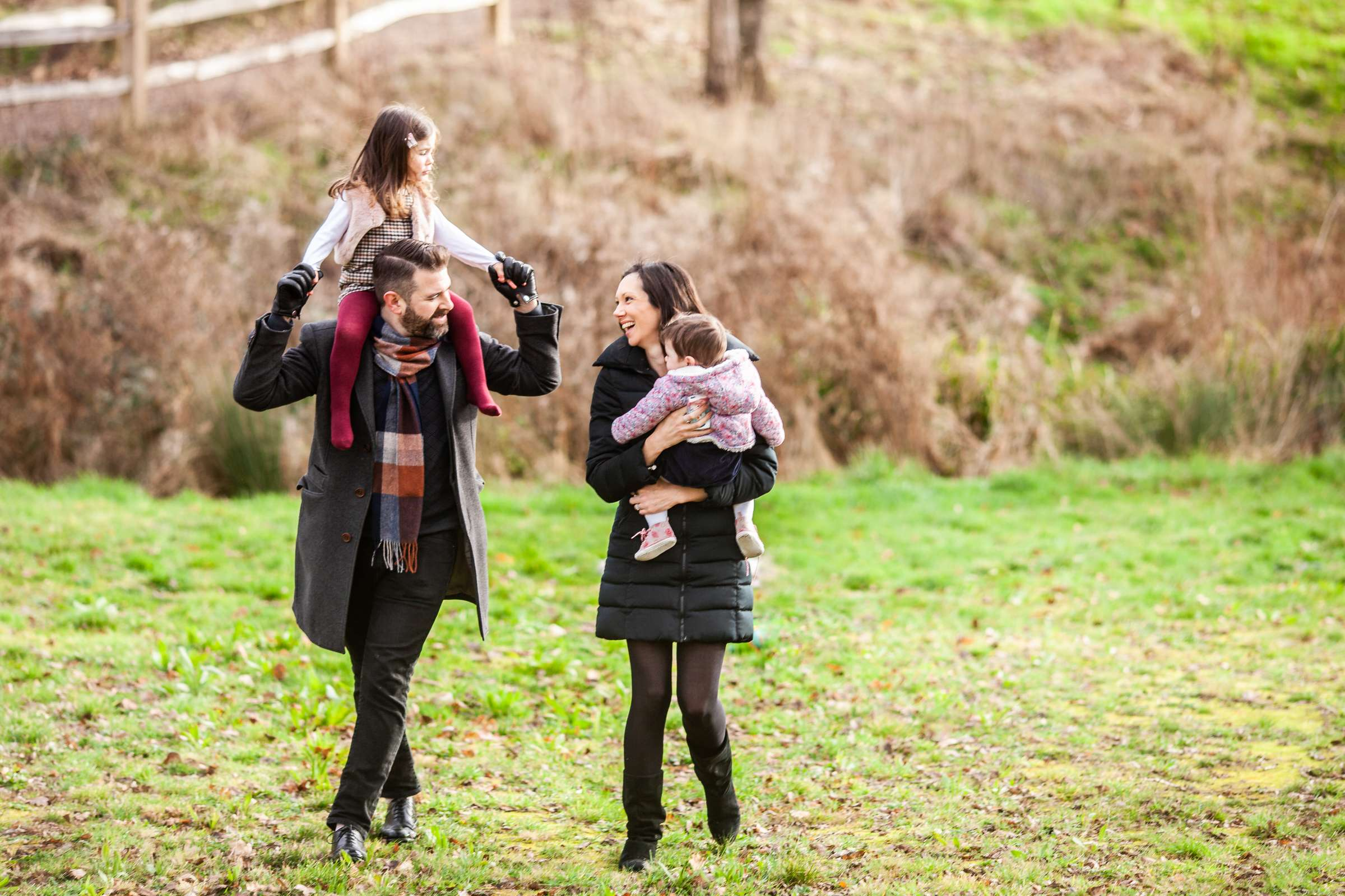 An outdoor portrait photo of a family with a baby and child walking wearing winter coats
