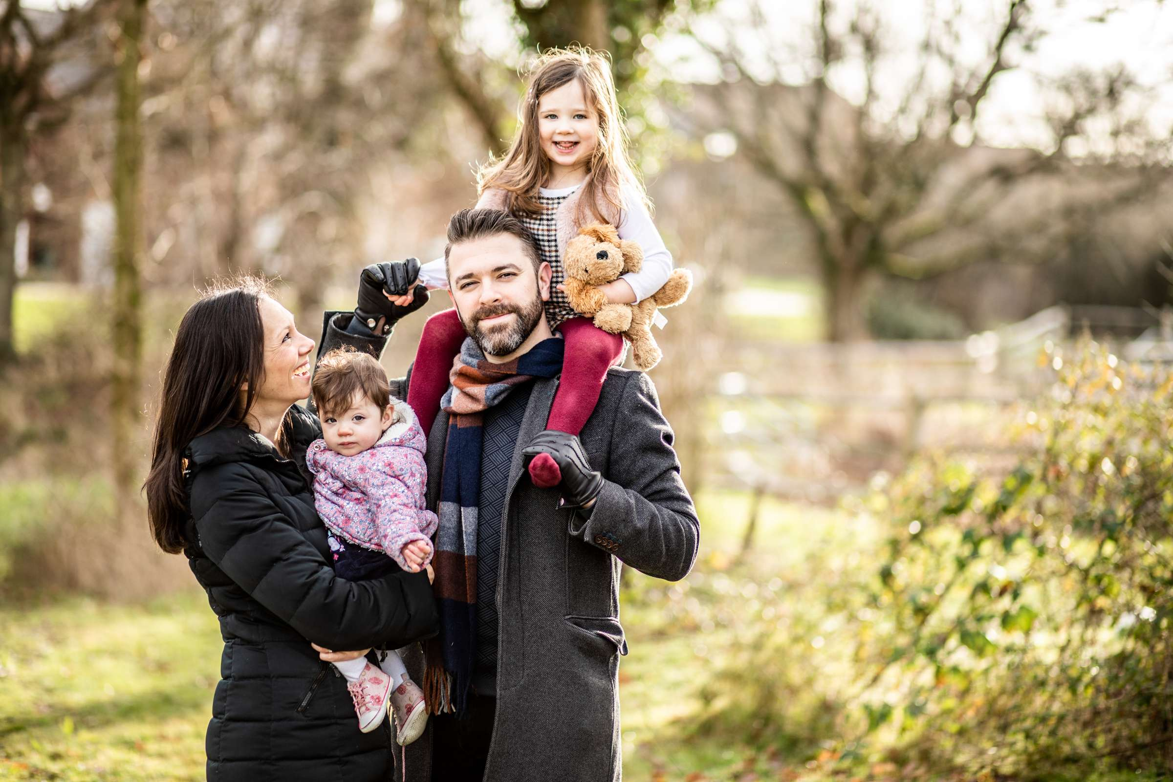 An outdoor portrait photo of a family with a baby and child wearing winter coats