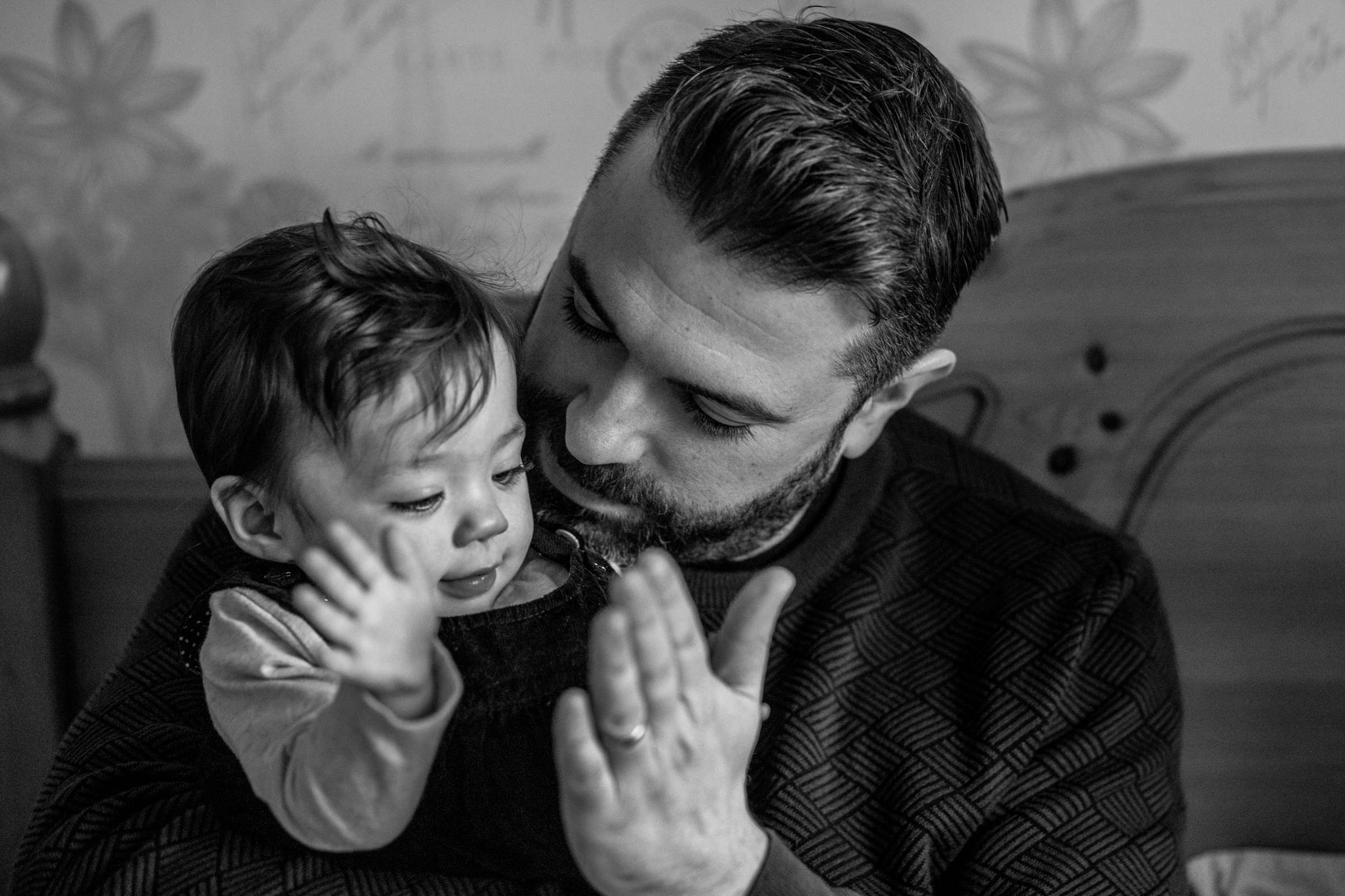 A black and white indoor portrait photo of dad and baby doing a high five