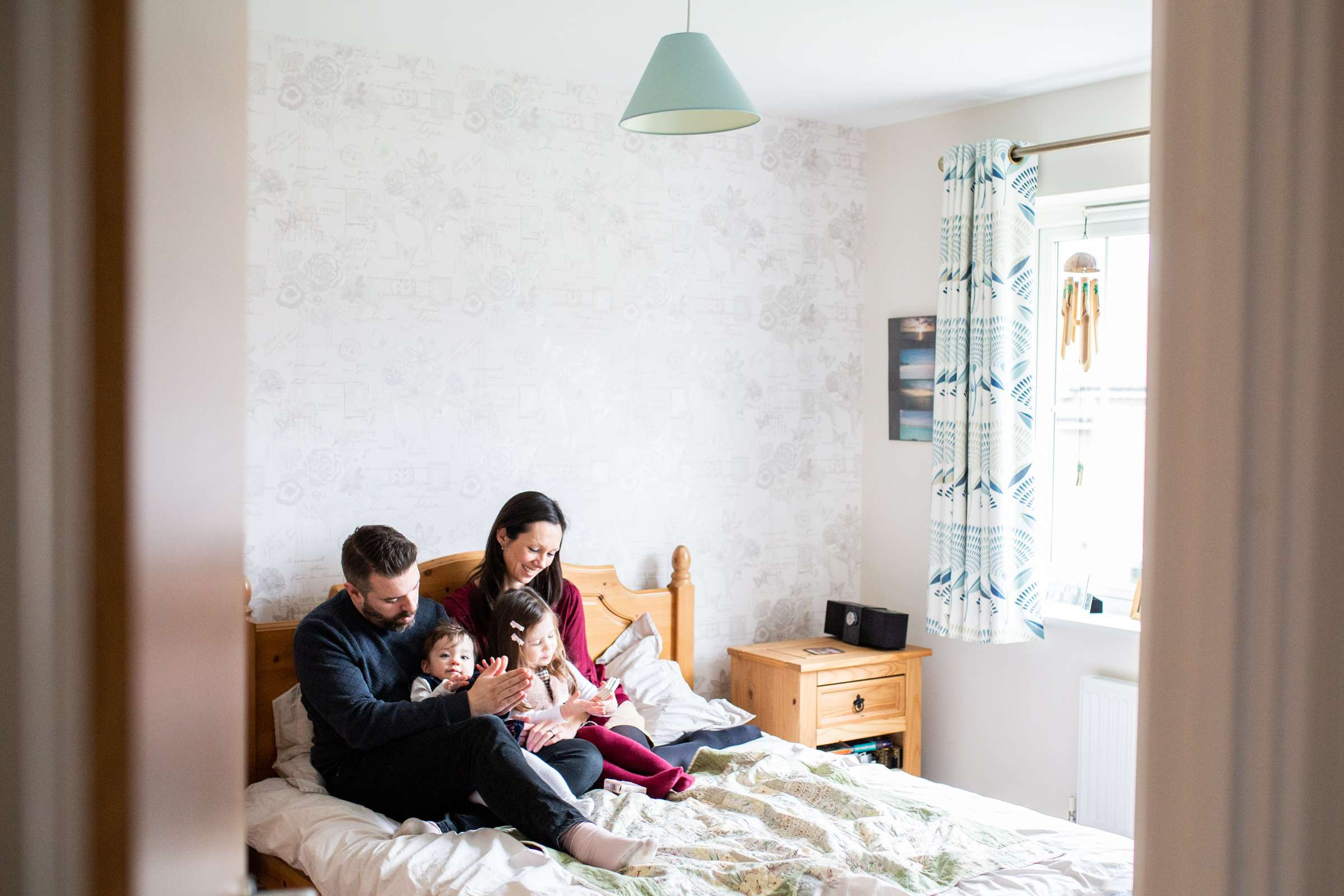 An indoor portrait photo of a family with two small children cuddling on the bed