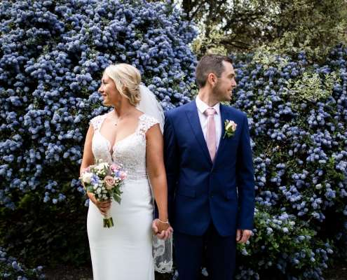 A wedding photo mid length of a bride and groom in front of a blue-flowered bush