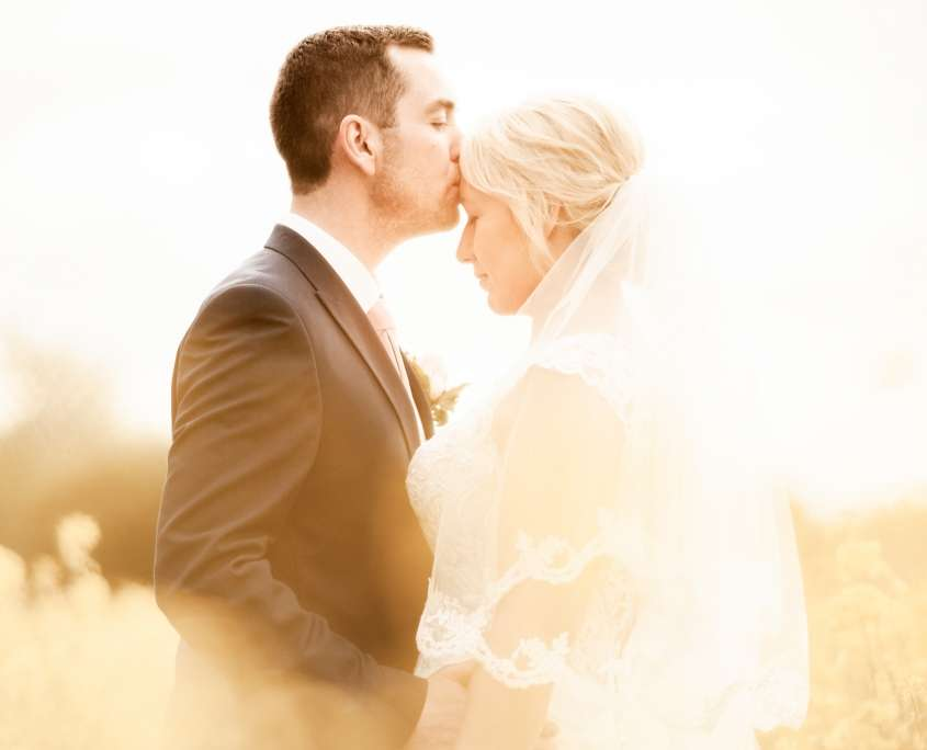 A wedding photo mid length of a bride and groom in a yellow field