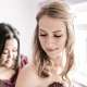 A wedding photo of two bridesmaids getting ready wearing sequinned maroon bridesmaids dresses